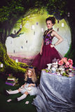 Little girl as Alice in Wonderland and evil queen. Little sitting on the floor girl in a beautiful dress in the image of Alice in Wonderland and the evil queen Stock Photos