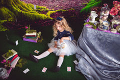 Little girl as Alice in Wonderland pouring tea. Little sitting on the floor girl in a beautiful dress in the image of Alice in Wonderland pouring tea Royalty Free Stock Photos