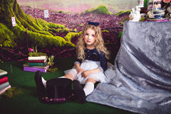 Little girl as Alice in Wonderland sitting on the floor Stock Photos