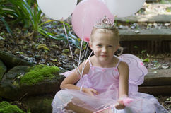 Little girl as a fairy-tale ballet princess. Little girl dressing up as a fairy-tale ballet princess on her birthday in forest garden royalty free stock photo