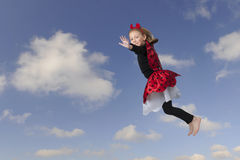 Little girl as a flying lady bug, blue sky with clouds Stock Photo