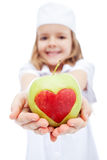 Little girl as nurse giving you an apple Stock Image