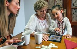 Little girl asking permission to continue playing tablet. Little girl asking permission to her mother to continue playing the tablet with her grandmother royalty free stock image