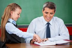 Little Girl Asking Question To Male Teacher At. Side view of little girl asking question to male teacher at desk in classroom Stock Photography