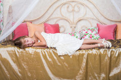 Little girl asleep on a bed in the clothing Royalty Free Stock Photography
