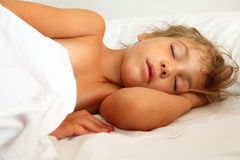 Little girl asleep in bed on sheet and pillow. Beautiful little girl asleep in bed on white sheet and pillow Royalty Free Stock Photos