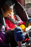 Little Girl Asleep and Drooling in Her Carseat on a Roadtrip. A little, blond girl on a roadtrip has fallen asleep and is drooling in her carseat.  she has an Royalty Free Stock Images