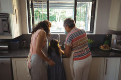 Little girl assisting mother and grandmother to wash utensil in kitchen Royalty Free Stock Photos
