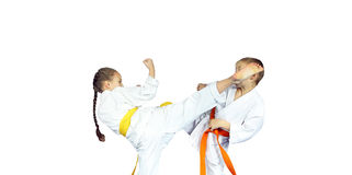 Little girl athlete in karategi  is beating to athlete leg on the head Royalty Free Stock Images
