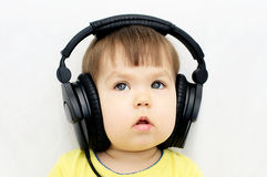 Little girl attentively listening with headphones Stock Photos