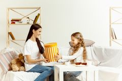 Little girl, attractive young mother are sitting at home royalty free stock photo