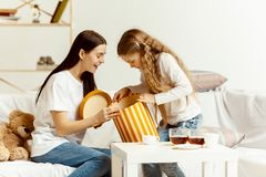 Little girl, attractive young mother are sitting at home stock image