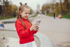Little girl in a autumn city. A little pretty girl with long blond hair and a red sweater standing in an autumn cloudy city and holding a phone stock photos