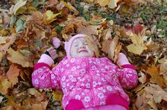 Little girl in autumn foliage Royalty Free Stock Photos