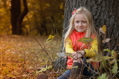 Little girl in the autumn forest Stock Image