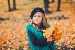 Little girl at autumn holding leaves. The little girl in the brown beret in autumn Park stock photo