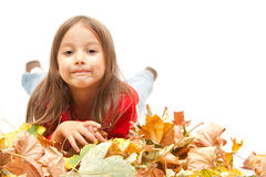 Little girl in autumn leaves Stock Image