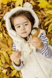 Little girl at the autumn leaves Stock Photos