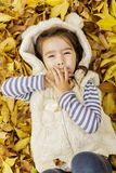 Little girl at the autumn leaves Royalty Free Stock Photo