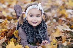 Little girl with autumn leaves in the park Royalty Free Stock Photo