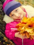 Little girl with autumn orange leaves stock photo