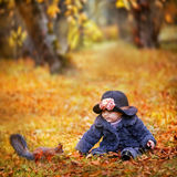 Little girl in autumn park. Little girl with squirrel in autumn park stock photography