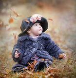 Little girl in autumn park. Little girl playing with leaves in autumn park royalty free stock photography