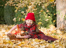 Little girl in autumn park with apple basket Stock Photo