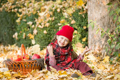 Little girl in autumn park with apple basket Stock Photography