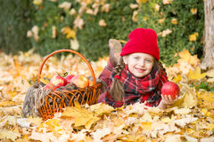 Little girl in autumn park with apple Stock Photography