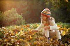 Little girl in an autumn park stock photo