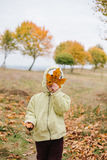 Little girl in the autumn park.face hidden behind dry leaf Stock Photo