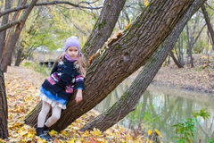 Little girl in autumn park on fall day outdoors Royalty Free Stock Images