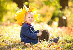 Little girl in the autumn park. Happy little girl with a wreath of autumn leaves stock photo