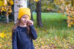 Little girl in autumn park outdoors Stock Photo