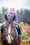 Little girl sitting on horse Royalty Free Stock Photos