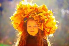 Little girl in autumn park in the sunlight Stock Image