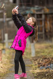 Little girl in autumn/spring clothes makes selfie on phone Stock Images