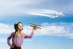 Girl in helmet pilot playing with a toy airplane Stock Photos