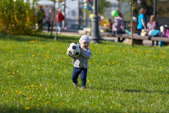 Little girl baby blond  Outdoors. Active football Stock Images