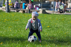 Little girl baby blond  Outdoors. Active football. Little active football fan running on the green grass field with ball Royalty Free Stock Photo