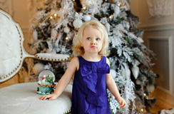 Little girl baby blonde in a blue dress with displeasure pouted. On the background of Christmas decorations Stock Photo