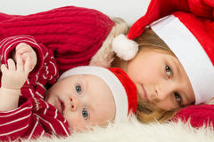 Little girl with baby boy lie in the hats of Santa Claus. Focus on a baby stock photography