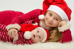 Little girl with baby boy lie in the hats of Santa Claus Royalty Free Stock Photos