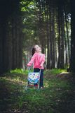 Little girl with baby carriage in forest Royalty Free Stock Images