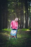 Little girl with baby carriage in forest Royalty Free Stock Photo