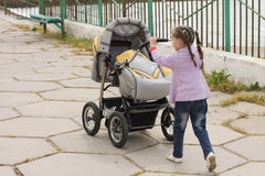 Little girl with baby carriages.  Stock Images