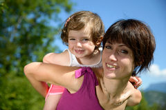A little girl in a baby carrier walks with his mom Stock Image