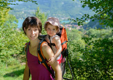 A little girl in a baby carrier walks with his mom. In the mountain stock photography