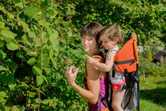 A little girl in a baby carrier walks with his mom. In mountain Royalty Free Stock Images
